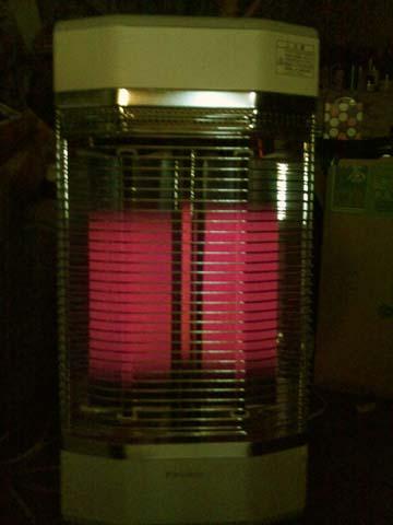 部屋を真っ暗にしてみるとダイキン(DAIKIN)の遠赤外線暖房機セラムヒート(ERFT11LS)は3本の発熱管が赤くなっているのが分かる